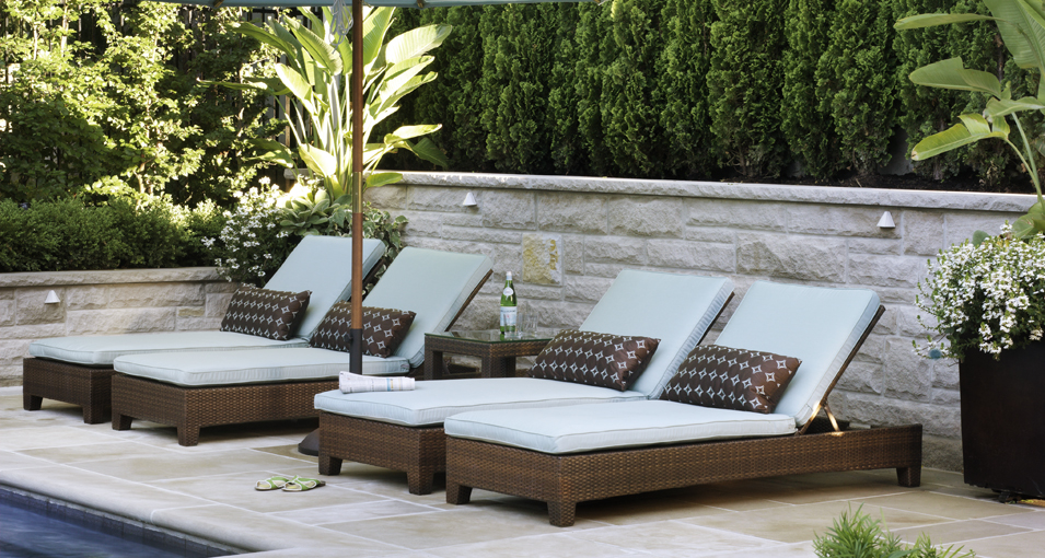 Photo slideshow of Artistic Gardens' design projects: loungers with patio umbrella arranged on flagstone terrace by swimming pool